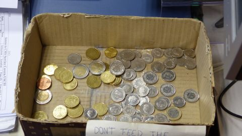 """""""Don't feed the physicists"""" marks a box of coins where CMS scientists deposit change to pay for coffee."""