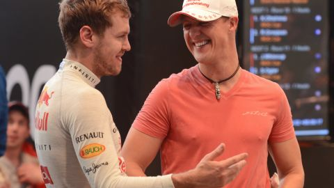 German Formula One driver and seven times world champion Michael Schumacher (R) talks with Formula One world champion Sebastian Vettel (L) during a warm-up for the Race of Champions (ROC) at Rajamangala Stadium in Bangkok on December 16, 2012. The Race of Champions (ROC) will take place in Thailand between December 14 and 16 and brings together heavyweights from all motor racing disciplines in the same type of car. AFP PHOTO / PORNCHAI KITTIWONGSAKUL (Photo credit should read PORNCHAI KITTIWONGSAKUL/AFP/Getty Images