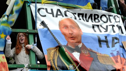 """A young protester shouts slogans near a placard depicting Russian President Vladimir Putin and signed """"Fare you well!"""" during the December 8 rally."""