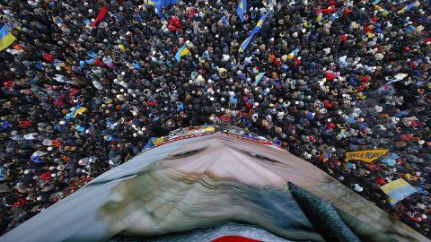 Pro-EU activists gather around a huge poster of Yulia Tymoshenko, the jailed former Ukrainian Prime Minister, on December 8.