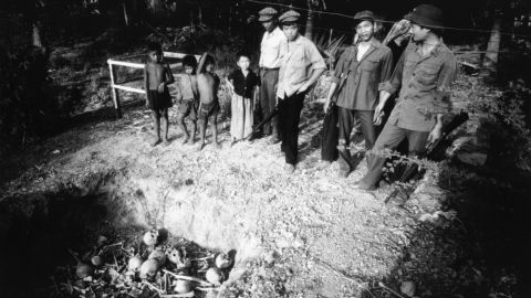 Cambodian civilians and Vietnamese soldiers open mass graves in 1979.