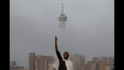 A mourner prays on a hill overlooking Johannesburg on Sunday, December 8.