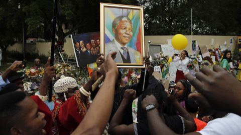 Mourners sing outside the home of former South African President Nelson Mandela in Johannesburg, South Africa, on Monday, December 9.