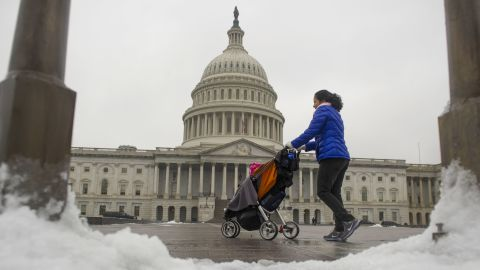 A woman strolls past the Capitol Building in Washington on December 9, after an overnight ice storm hit the region. Federal agencies opened two hours late because of the weather.