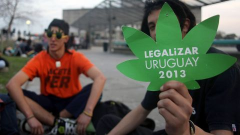 Youngsters wait outside the Parliament building (background) while lawmakers debate the bill legalizing marijuana, in Montevideo, on July 31, 2013.