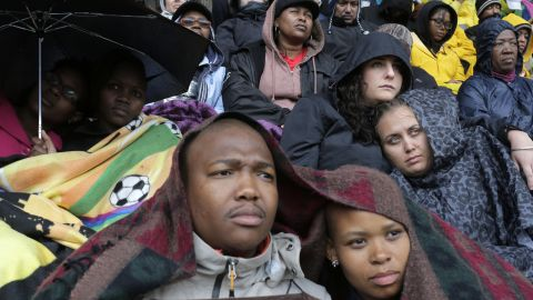 People take shelter under blankets and umbrellas during the memorial service.