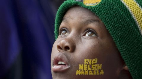 """A boy looks up during the memorial service at FNB Stadium. He has """"RIP Nelson Mandela"""" painted on his face."""