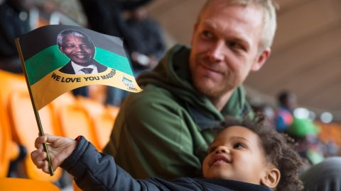 """A young boy holds up a flag honoring """"Madiba,"""" Mandela's traditional clan name."""