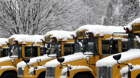 Snow covers buses for the Baltimore County Public Schools in Towson, Maryland, on Tuesday, December 10. Snow and ice snarled travel across parts of the United States, hitting major airline hubs in the Northeast.