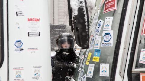 A young police officer guards a roadblock on Institutskaya Street near the presidential area in Kiev on December 11.