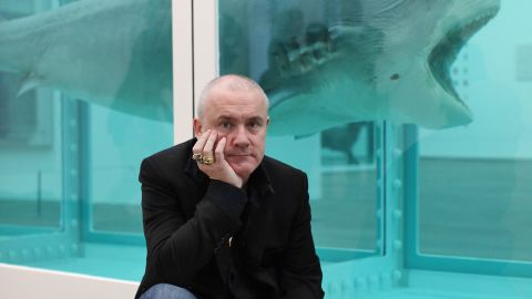 """Damien Hirst, seen here in front of one of his most famous artworks, """"The Physical Impossibility of Death in the Mind of Someone Living"""" - a shark preserved in formaldehyde - was the subject of a major retrospective at London's Tate Modern gallery in 2012."""
