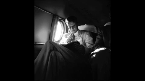 """Graham reads on an airplane during a """"Pulpit in the Sky"""" trip in 1953."""