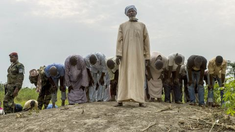 People pray as they bury 16 coffins in a Muslim cemetery in Bangui on December 11.