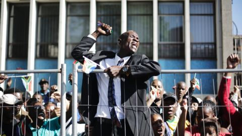 A cheering man climbs up a fence after the casket of Mandela passed on its way to the Union Buildings on December 13.