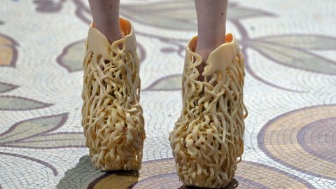 """Iris van Herpen and architect Rem D Koolhaas collaborated to create 3-D-printed shoes that resemble tree roots. The intricate lattices that wrap around the foot would not have been possible without 3-D printing. As Koolhaas says: """"They are almost like a sculpture on your feet."""""""