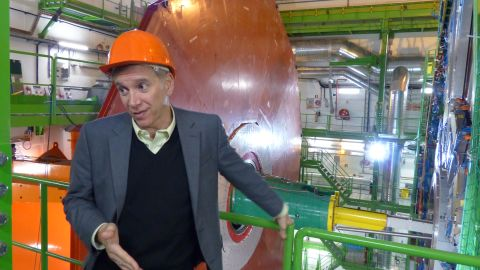 Joe Incandela, the spokesperson for CMS, says that about 4,000 scientists collaborate on the experiment. Behind him is a new red-colored layer to improve the detection of muons, which are fundamental particles