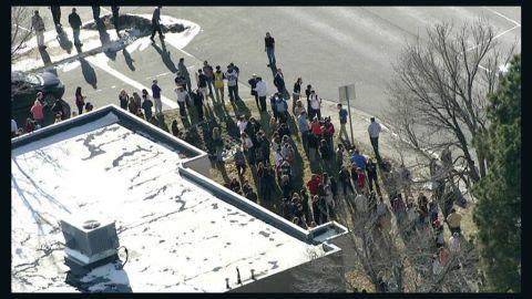 People gather outside the Arapahoe Highschool in Centennial, Colorado, on December 13.