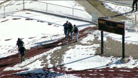 Members of law enforcement are seen outside the school.