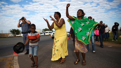 Women sing and dance after the hearse arrived at Waterkloof air base.