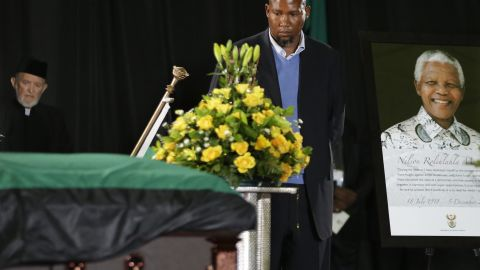 Mandela's grandson Mandla Mandela walks by his grandfather's casket during a farewell ceremony at Waterkloof air base.