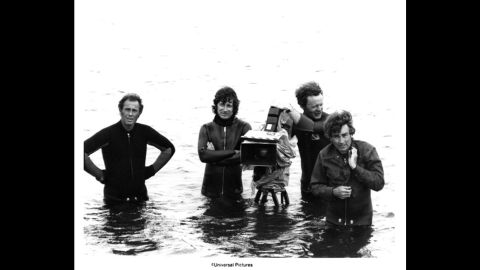 """Spielberg, arms crossed, and his camera crew wade in water on the set of """"Jaws"""" at Martha's Vineyard in Massachusetts. The 1975 film made $60 million in its first month, which in 2013 dollars would be equal to about $256 million. """"Jaws"""" was the highest-grossing movie of all time until """"Star Wars."""""""