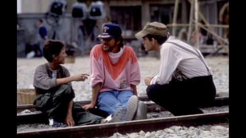 """Actor Christian Bale, left, Spielberg and John Malkovich talk on the set of """"Empire of the Sun"""" in 1987. The film is taken from J.G. Ballard's novel based on Ballard's experiences as a boy in a Japanese prison camp during World War II."""