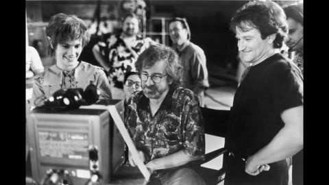 """Actors Julia Roberts and Robin Williams watch production footage with Spielberg on the set of the film """"Hook"""" in 1991."""