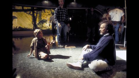"""Spielberg sits with child actor Joseph Mazzello during the filming of """"Jurassic Park"""" in 1993. The film, based on the science-fiction novel by Michael Crichton, is Spielberg's highest-grossing movie to date. It has made more than $914 million."""