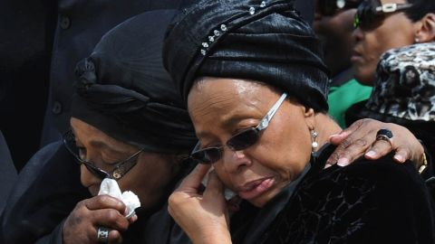 Nelson Mandela's widow Graca Machel, right, and Winnie Madikizela-Mandela, his former wife, wipe their tears as the former president's casket arrives at Mthatha Airport on December 14.