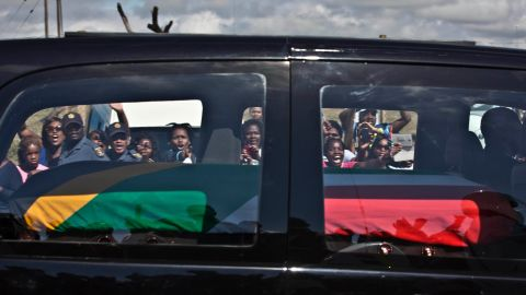 Mourners wave and cheer as the hearse carrying Mandela's body passes through the town of Mthatha on Saturday, December 14.