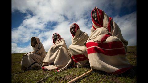 Men sit on a hillside overlooking the hometown of Mandela on December 14.