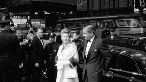 """Fontaine, escorted by Charles Addams, arrives at the Rivoli Theater in 1963 for the world premiere of the film """"Cleopatra"""" in New York."""