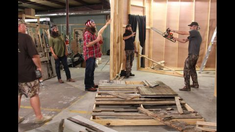 """The Duck Commander crew works on transforming their warehouse into a """"scarehouse"""" during a Halloween episode. Holding the chainsaw is Si Robertson, who founded the company along with his brother Phil, not pictured."""