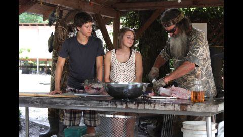 """Phil Robertson cuts meat during a recent """"Duck Dynasty"""" episode. He was <a href=""""http://www.cnn.com/2013/12/19/showbiz/duck-dynasty-suspension/index.html"""">suspended by A&E</a> in December 2013 after he made controversial remarks about gays and blacks in an interview with GQ magazine."""