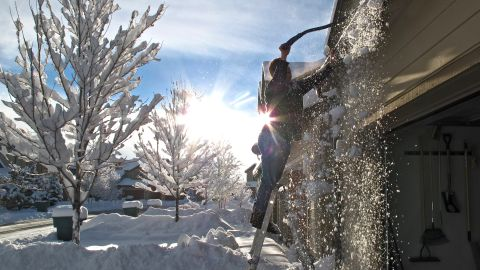 Keola Wong removes snow from the roof of his Bellemont, Arizona, home on Friday, December 20. A storm system dropped heavy snow in northern Arizona, while Phoenix-area streets and highways were wet from rain during the morning commute.