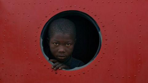 A boy looks out the broken window of a plane being used as shelter at M'Poko International Airport on December 21.