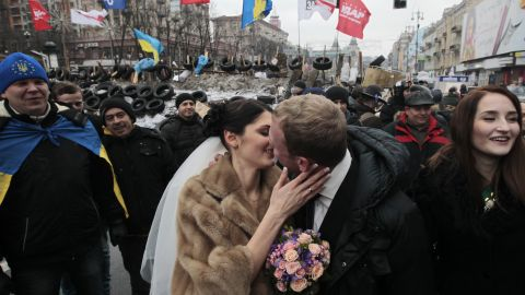 Newlyweds Mikhail and Margarita Nakonechniy kiss in front of barricades on Independence Square in a gesture of support for pro-Europe activists in Kiev, Ukraine, on Saturday, December 21. Protesters have poured into the streets of the Ukrainian capital, angered by their government's move away from the European Union in favor of closer ties with Russia.