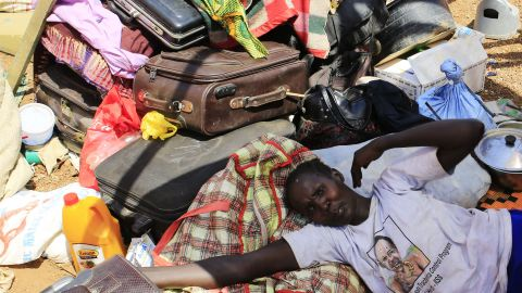 A mother displaced by recent fighting in South Sudan rests on top of her belongings in a makeshift U.N. shelter on Monday, December 23.