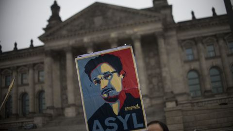 Campact activists hold up a portrait of US whistleblower Edward Snowden in front of the Reichstag building housing the Bundestag (lower house of parliament) in Berlin on November 18, 2013. German MPs were to hold a session at the Bundestag, focusing on the spying methods of the US National Security Agency (NSA) and its impact on Germany and transatlantic relationship. Snowden, former NSA contractor, had said before he was ready to help Germany following revelations, based on documents he provided, that have included the tapping of German Chancellor Angela Merkel's phone