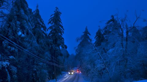 Utility crews prepare to work on power lines at dusk in Litchfield, Maine, on Thursday, December 26. Many have been without electricity since Monday's ice storm, up to 7 inches of snow is forecast, worrying utilities that the additional weight on branches and transmission lines could cause setbacks in the around-the-clock efforts to restore power.