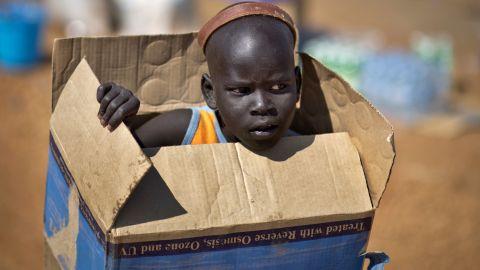 A displaced boy carries a cardboard box inside a U.N. compound in Juba on Friday, December 27.