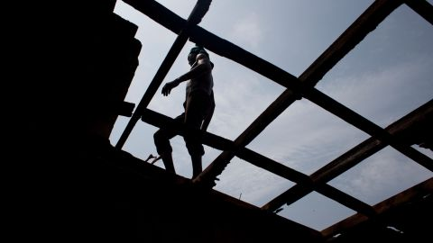 A man walks on a roof beam in Bangui on December 28 as local residents tear apart a house said to have belonged to a Seleka officer.