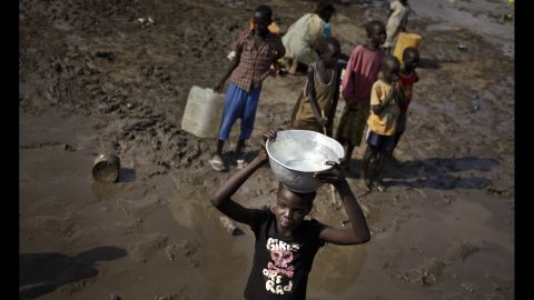 A girl carries a bowl of water after filling it from a truck at the U.N. compound in Juba on December 29.