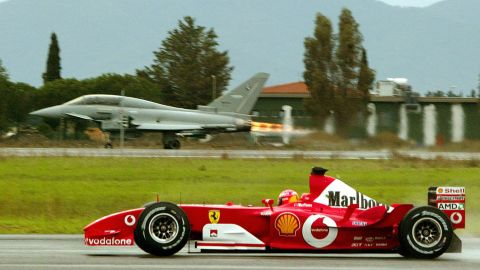 Schumacher steers his Ferrari in front of a Eurofighter on the track of a military airport in Grosseto, Italy, in 2003.