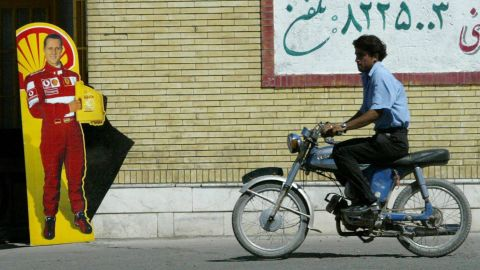 A man rides past a poster with Schumacher's likeness in Bahreman, Iran, in 2005.