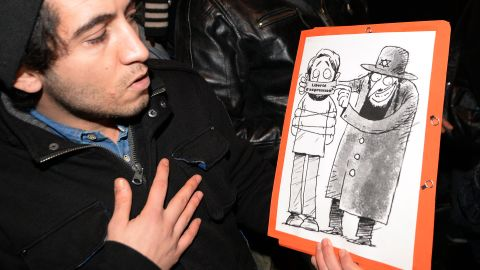 """Supporters of Dieudonne  argue that the issue of """"freedom of speech"""" in France is at stake after Valls called for the comic's performances to be banned. Here a man poses with one of his drawings showing a Jewish character covering the mouth of another character with a gag reading """"freedom of speech."""""""
