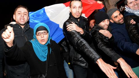 """The """"quenelle"""" gesture has been popularized by the anti-establishment French comedian Dieudonne, who has been condemned in France for anti-Semitism. Here people perform the """"quenelle"""" in front of  Dieudonne's theater, while protesting against French interior minister Manuel Valls who has called for Dieudonne's performances to be banned."""