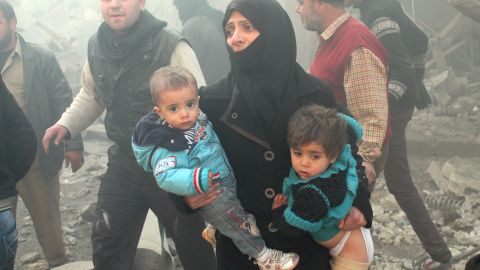 A Syrian woman carries children following airstrikes on Aleppo on December 15.