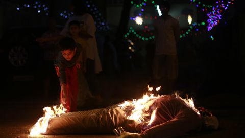 In Mumbai, an Indian boy lights the effigy of an old man, symbolizing the burning of the past in hopes of starting a new year without bad memories.