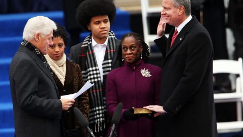 New York City's 109th Mayor, Bill de Blasio, right, is sworn in by former President Bill Clinton, left, as his family watches on Wednesday, January 1 in New York City.
